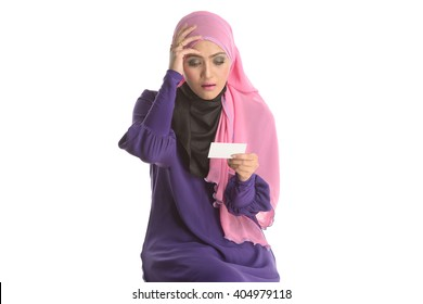 a portrait of young beautiful asian muslim woman holding a card in case of headache. Isolated white