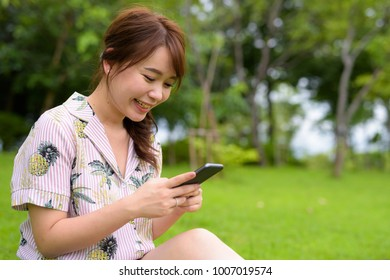 Portrait of young beautiful Asian tourist woman relaxing at the park