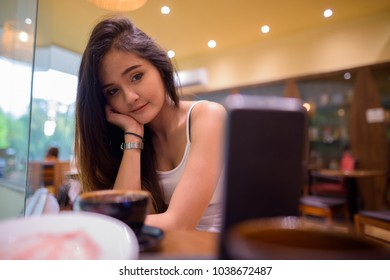 Portrait of young beautiful Asian tourist woman exploring Ho Chi Minh city in Vietnam