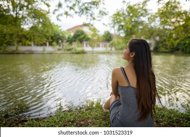Portrait of young beautiful Asian woman relaxing by the lake at the park