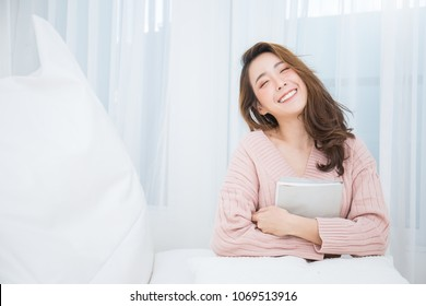Portrait of young beautiful asian woman relax holding book in her bedroom. Smile happy asian girl relaxing in cold winter concept