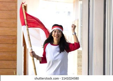 portrait of young beautiful asian woman with indonesian flag. independence day