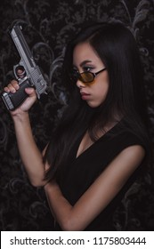 Portrait of young beautiful asian woman with pistols