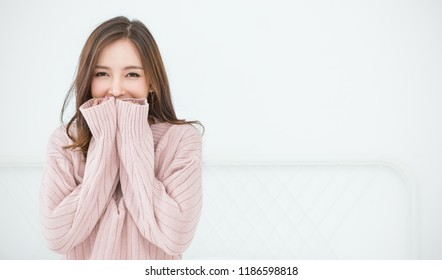 Portrait of young beautiful asian woman relax bedroom. Smile happy asian girl hands cover face wear winter cloth. Beauty treatment perfect clear skin japanese woman makeup winter hygge concept banner