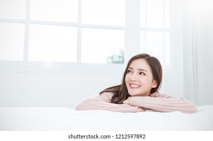 Portrait young beautiful asian woman relax in bedroom. Smile happy face asian girl look up on white background. Beauty treatment perfect clear skin japanese makeup relax, Asia hygge lifestyle concept