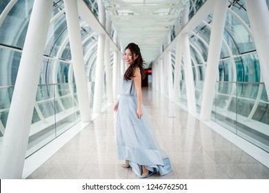 Portrait of a young and beautiful Asian woman in a princess blue dress walking across a futuristic bridge during the day. She is smiling as she strolls and looks at the camera.