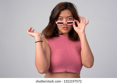 Portrait of young beautiful Asian woman removing novelty glasses