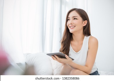 Portrait of young beautiful asian woman relax using smartphone gadget in her bedroom. Smile happy asian girl online shopping at home. Education e-commerce freelance technology connected people concept