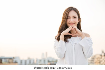 Portrait of young beautiful asian woman hands gesture in heart shape on city sky roof top. Smile face asian girl wear casual cloth. Japanese girl lifestyle, lovely woman valentines' day concept