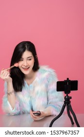 Portrait of young beautiful asian woman professional beauty vlogger or blogger recording to share on social media by smartphone on tripod. Cute model in studio on pink background.
