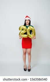 Portrait of young beautiful asian woman in fashion dress posing with gold 20 twenty number balloons isolated white background. Christmas and new year Credit and deposit installments concept.