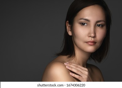 Portrait of young and beautiful asian woman on gray background