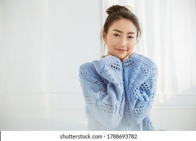 Portrait der jungen schönen asiatischen Frau entspannen Gesicht im Winterzimmer. Nahaufnahme sexy Beauty Fashion Mädchen gesunde Make-up Gesichtsbehandlung perfekte glatte Haut. Lächeln glücklich asia koreanisches Mädchen ist kalt.