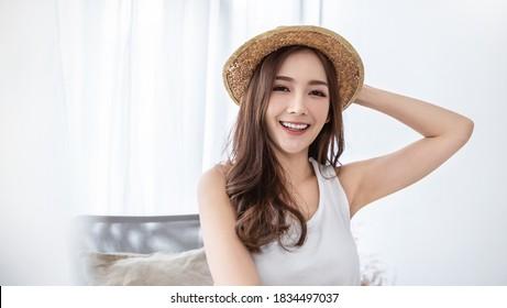 Portrait von jungen schönen asiatischen Frau im Urlaub Sommerzeit in weißen Schlafzimmer. Fröhliches Mädchen im Sommer. Koreanische Hautpflege. Fashion Lifestyle-Konzept der Universität