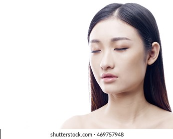 portrait of a young and beautiful asian woman, eyes closed, isolated on white background.