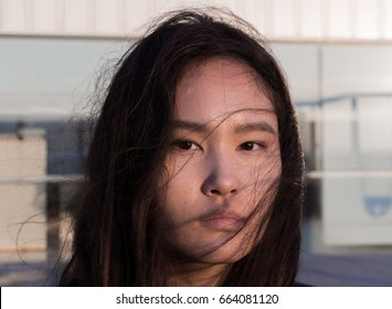 Portrait of young beautiful asian woman looking in camera on the wind