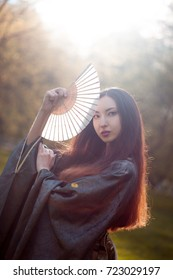 Portrait of young beautiful Asians in grey kimono and with a fan