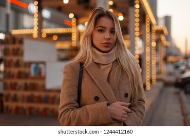 Portrait of a young beautiful attractive blonde woman in a stylish beige vintage coat and fashionable knitted warm sweater on the festive city. Sexy stylish girl. Urban style