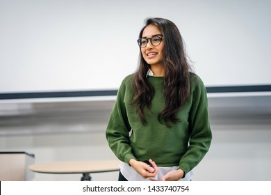 Portrait of a young, beautiful, attractive and intelligent Indian Asian woman wearing spectacles in a sweater giving a presentation in a lecture classroom. She is smiling as she is presenting.