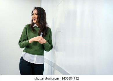 Portrait of a young, beautiful, attractive and intelligent looking Indian Asian businesswoman explaining a concept by sketching on a whiteboard. She is wearing a preppy green sweater and glasses.
