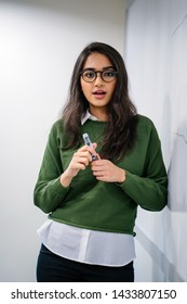 Portrait of a young, beautiful, attractive and intelligent looking Indian Asian lecturer or student explaining a concept by sketching on a whiteboard. She is wearing a preppy outfit and spectacles.