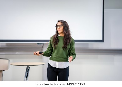 Portrait of a young, beautiful, attractive and intelligent-looking Indian Asian woman wearing spectacles in a sweater giving a business presentation to an audience.