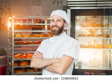 Portrait of a young beautiful baker with fresh bread and an oven in the background.