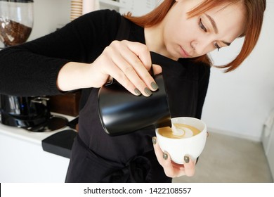 Portrait of young beautiful barista woman with red hair wearing stylish black apron making cappucino hot beverage in hipster coffee place. Close up, copy space, background.
