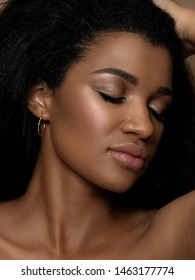 Portrait of young beautiful black woman touching her hair. Cleaning skin, SPA therapy, skincare, cosmetology and plastic surgery concept