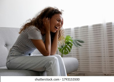 Portrait of young beautiful black woman experiencing excruciating migraine grabbing her head. Female expressing physical and emotional pain. Sad girl in her room. Background, copy space.