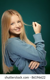 Portrait of young beautiful blond female over green background