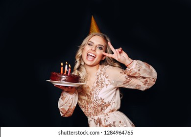 Portrait of a young beautiful blond girl holding birthday cake with candles and having fun