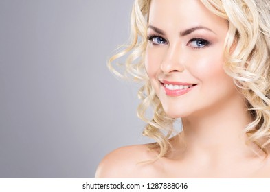 Portrait of young and beautiful blond girl with curly hair. Face lifting and beauty concept.