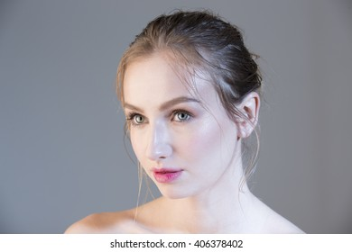 Portrait of young beautiful blond girl over gray background. Colorized.