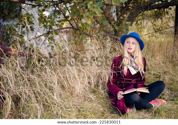portrait of young beautiful blond hipster woman reading paper book on sunny autumn day outdoors copy space background