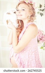 Portrait of young beautiful blond pregnant woman wearing in pink with white rabbit and pink flowers on her head. with long curly hair.