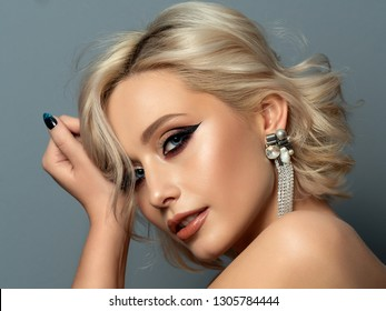 Portrait of young beautiful blond woman with evening make up touching her head. Modern fashion eyeliner wing and beautiful earring. Studio shot.