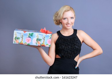 A portrait of a young beautiful blond woman model posing in black dress with a bright manicure and a hairstyle holding a present gift box smiling in studio