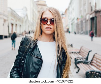Portrait of a young beautiful blonde girl with sunglasses walking on the streets of Europe. Outdoor. Warm color.