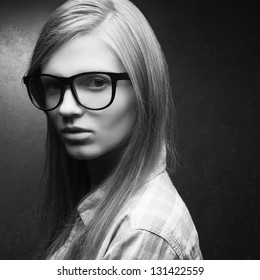 Portrait of a young beautiful blonde model wearing trendy glasses and casual shirt and posing over metal background. Hipster style. Close up. Copy-space. Monochrome studio shot.