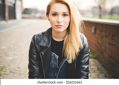 Portrait of young beautiful blonde straight hair woman in the city, looking in camera, pensive - wearing a black leather jacket - carefreeness, youth concept