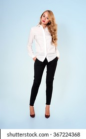 Portrait of young beautiful blonde in white blouse and black pants