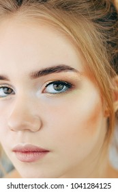 Portrait of young beautiful blonde woman with creative make up. Multicolored smokey eyes and perfect brows