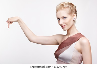 portrait of young beautiful blonde woman pointing down on something
