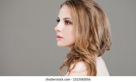 Portrait of a young beautiful blonde woman. Girl in white shirt on grey background, beautiful and charming