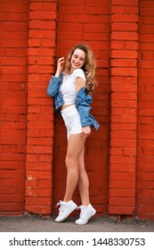 Portrait of a young beautiful blonde woman in white shorts and a vest posing against a beautiful brick wall
