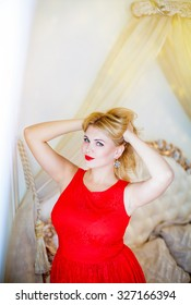 portrait of young beautiful blonde woman with red lips in red dress