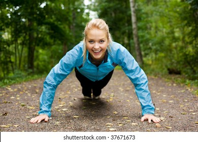 Portrait of a young beautiful blonde woman doing push-ups