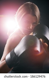 Portrait of Young beautiful boxing girl standing with a guard ready to punch. Black background with direct light with lens flare.