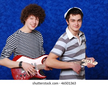 Portrait young beautiful boys in studio on a dark blue background
